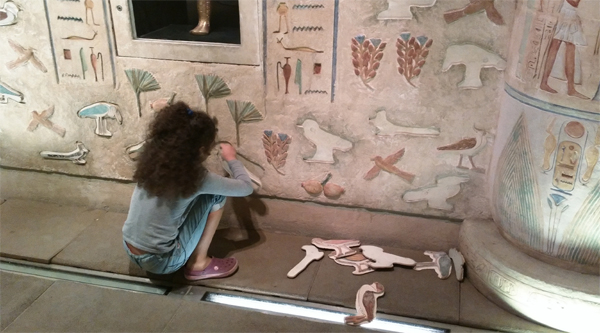 Decorating a wall with hieroglyphs.